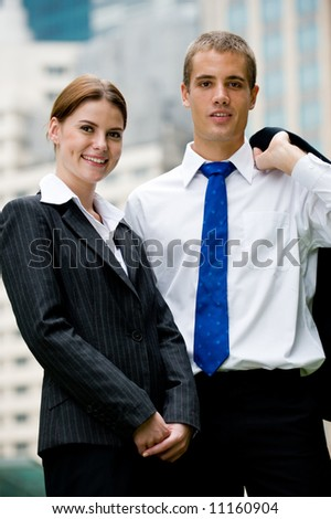 A businesswoman and man standing together outside in the city - stock photo