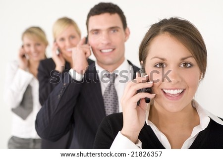 A businesswoman and three colleagues out of focus behind her all talking on cell phones
