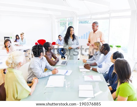 A Businesswoman Discussing in Front of her Colleagues - stock photo