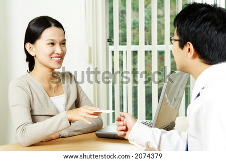 A businesswoman handing out a business card to a businessman