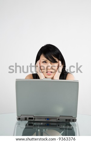 A businesswoman having a headache while working on her laptop - stock photo