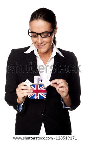 A businesswoman holding British twenty pond notes in a small perch as a savings concept. Pound saving. - stock photo