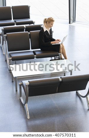 A businesswoman in waiting room, typing on a laptop - stock photo