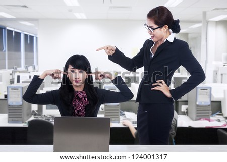 A businesswoman is bullying her subordinate in the office