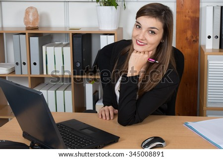 A businesswoman is concentrating on screen with pen in her hand