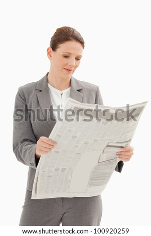 A businesswoman is reading a newspaper