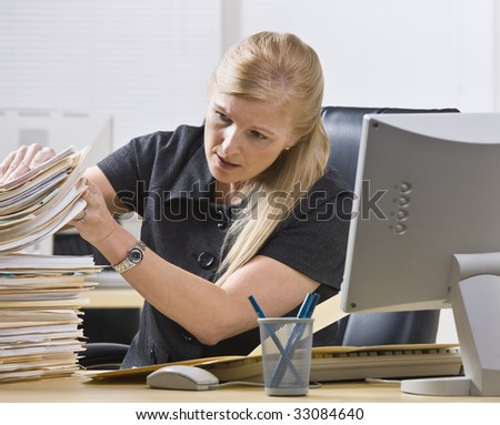 A businesswoman is seated at a desk in an office and is looking through a stack of paperwork.  Horizontally framed shot. - stock photo