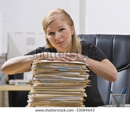 A businesswoman is seated at a desk with a large stack of paperwork in front of her.  She is looking at the camera.  Horizontally framed shot. - stock photo