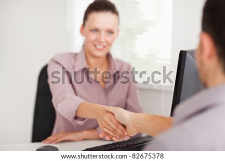 A businesswoman is shaking hands with a customer - stock photo