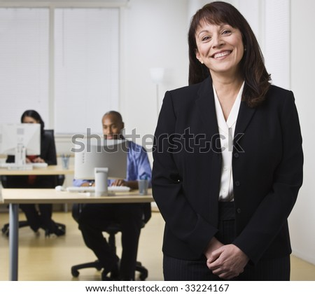 A businesswoman is standing in an office while her coworkers are seated at computer desks.  She is smiling at the camera.  Horizontally framed shot. - stock photo