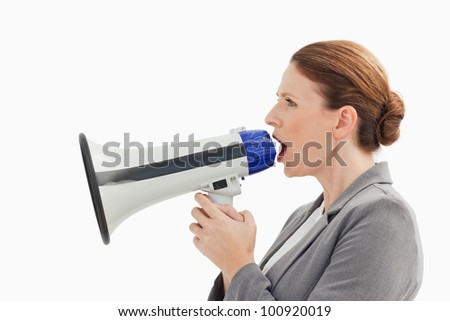 A businesswoman is talking into a megaphone