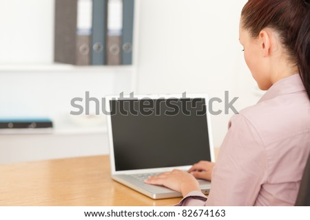 A businesswoman is typing on her notebook in her office