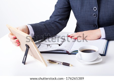 A businesswoman looking at a memorable photo while at her office - stock photo