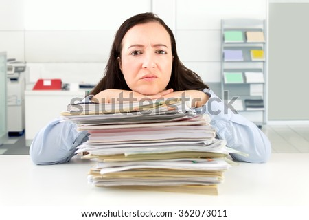A businesswoman looking overwhelmed while surrounded by paperwork in the office - stock photo