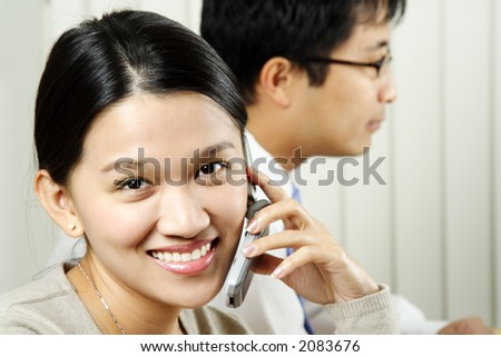 A businesswoman making a phone call with a businessman in the background