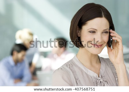 A businesswoman on a mobile phone, three colleagues in background having a discussion - stock photo