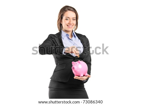 A businesswoman putting a coin into a piggy bank isolated on white background - stock photo
