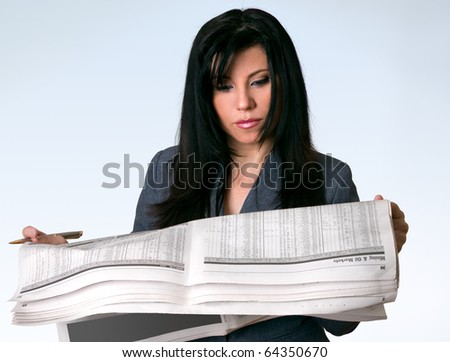 A businesswoman reading the finance section of a newspaper.