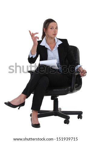 A businesswoman seated on a chair.