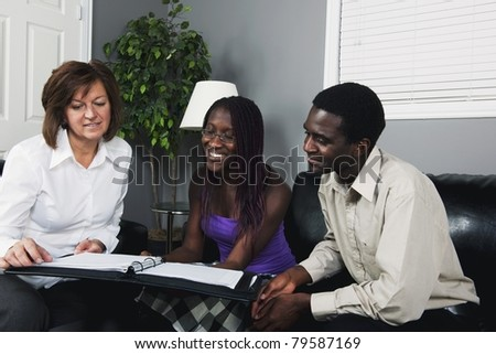 A Businesswoman Showing A Document To A Couple - stock photo