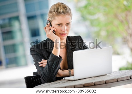 A businesswoman talking on her phone while using her laptop at an outdoor cafeteria - stock photo