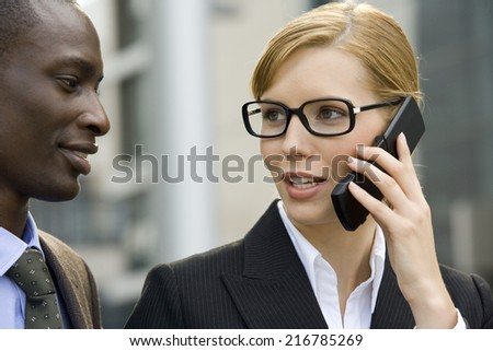 A businesswoman talks on the phone, man looks on.