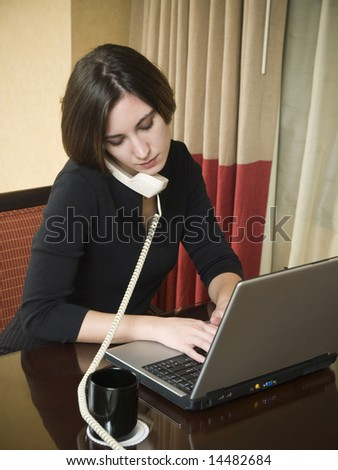 A businesswoman talks on the phone while working on her laptop computer in a hotel room during a business trip.