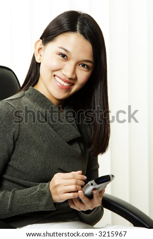 A businesswoman using her PDA at the office - stock photo