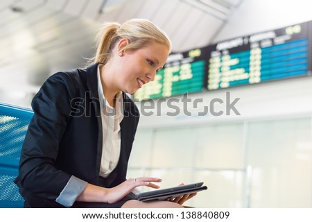 a businesswoman using her tablet computer at an airport. mobility and communication in business. roaming charges when abroad. - stock photo