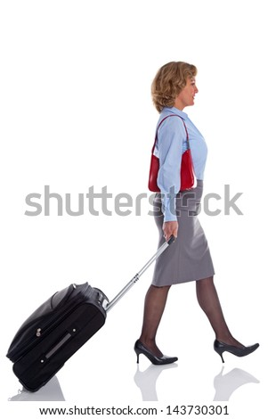 A businesswoman walking along pulling a suitcase, isolated on white background. - stock photo