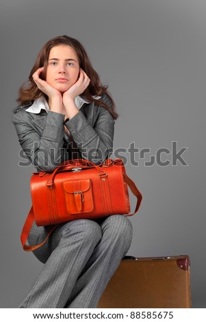 A businesswoman with a bag and a suitcase. On a gray background. - stock photo
