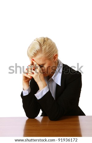 A businesswoman with a headache, sitting at the desk, isolated on white background