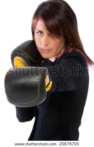 A businesswoman with box gloves ready to fight in the office - stock photo