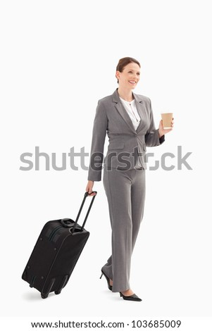 A businesswoman with coffee and a suitcase - stock photo