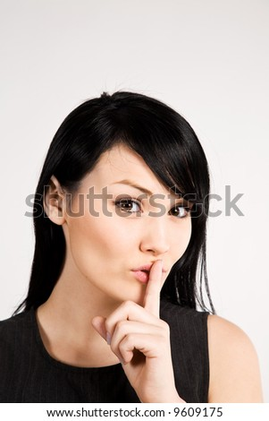 A businesswoman with her finger on her lips - stock photo