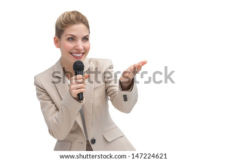 A businesswoman with microphone showing something with her hand - stock photo