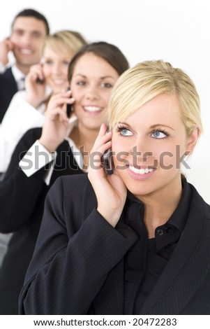 A businesswoman with three other executives out of focus behind her all talking on cell phones