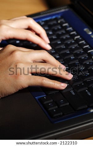 A businesswoman working and typing on her laptop