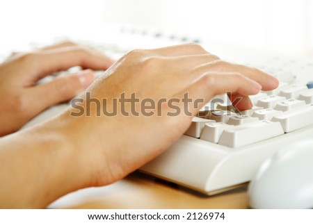 A businesswoman working and typing using a keyboard - stock photo