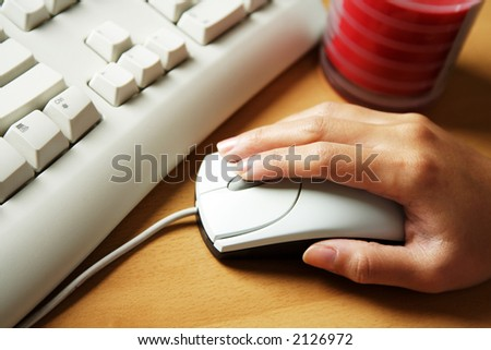 A businesswoman working in the office and clicking on her mouse - stock photo