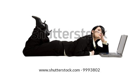 A businesswoman working on her laptop while lying down on the floor - stock photo