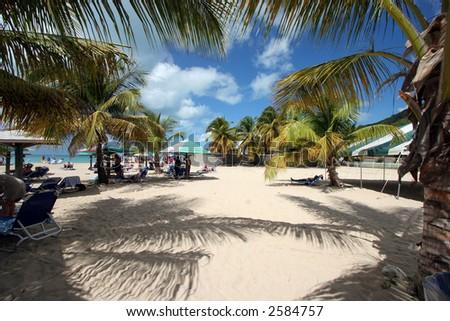 A busy beach in Antigua - stock photo