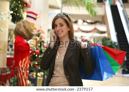 A busy woman Christmas shopping and talking on the phone - stock photo