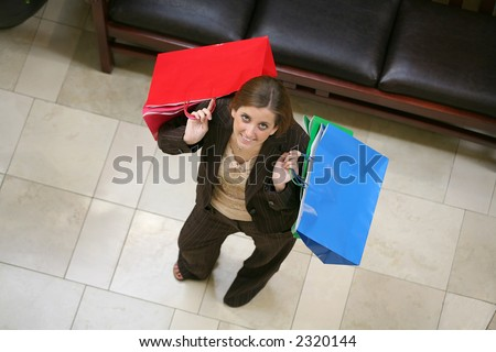 A busy woman shopping and holding several bags - stock photo