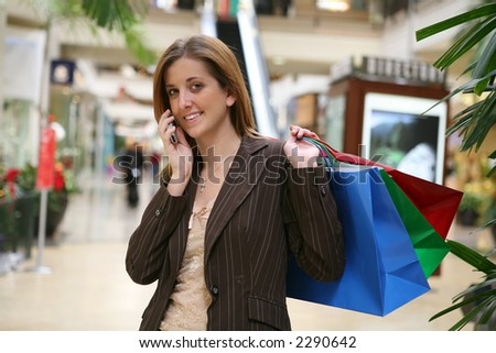 A busy woman shopping and talking on the phone - stock photo