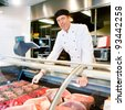 A butcher at a fresh meat counter or deli in a store - stock photo