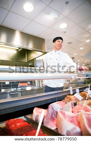 A butcher helping a customer at a fresh meat counter or deli - stock photo
