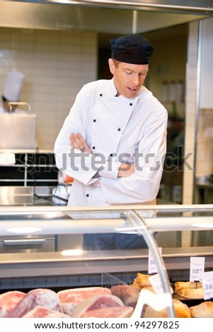 A butcher looking at the available meat in a grocery store - stock photo