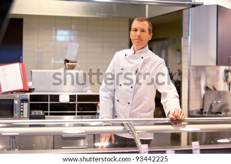 A butcher standing at a fresh meat counter in a grocery store - stock photo