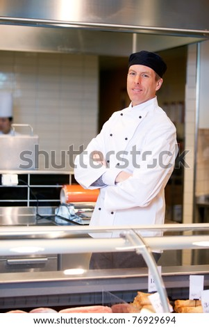 A butcher standing behind a fresh meat counter - stock photo